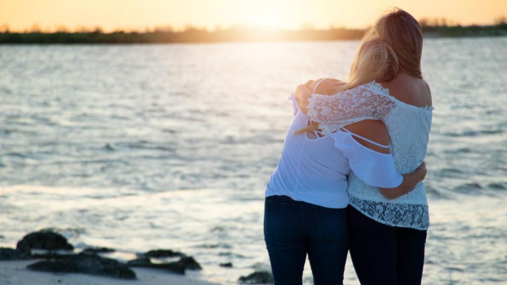 women embracing on the beach
